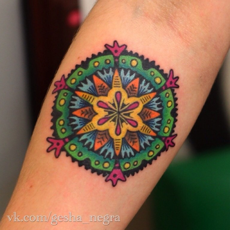 Small cartoon style colored ornamental flower tattoo on forearm