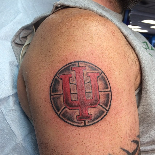Small circle shaped basketball tattoo on shoulder with symbol