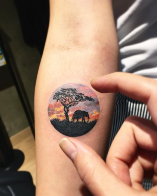 Small circle shaped colored forearm tattoo of elephant with lonely tree