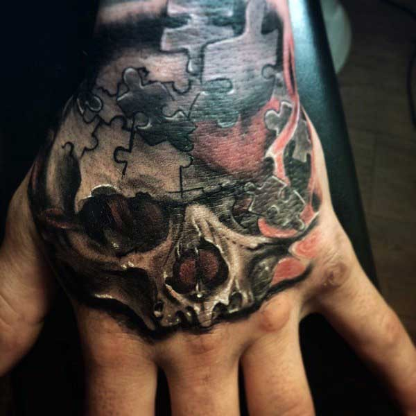 Small colored human skull tattoo stylized with puzzle pieces