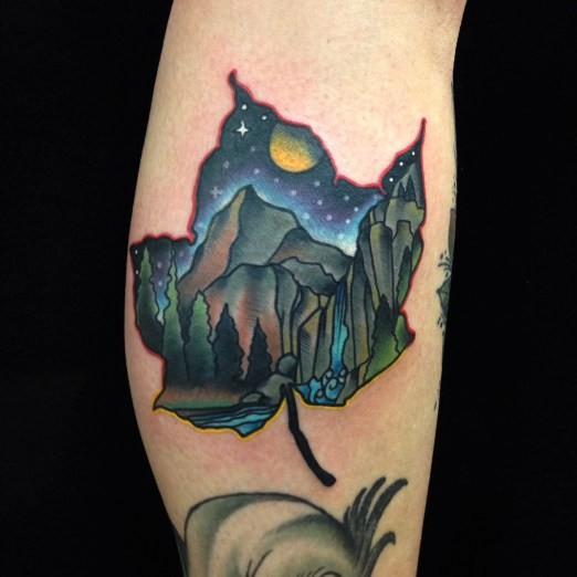 Small colored maple leaf shaped tattoo on leg stylized with night mountains