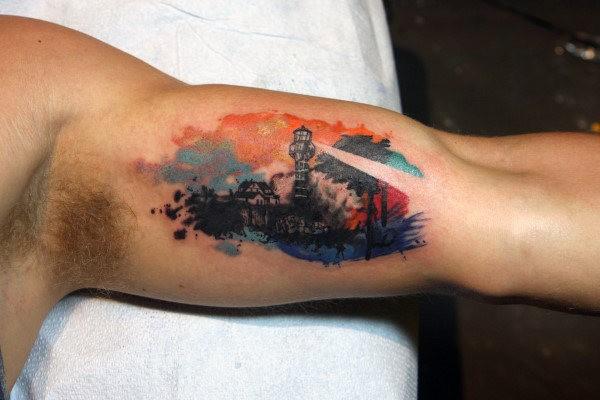 Piccolo tatuaggio bicipite colorato creativo di un grande faro funzionante