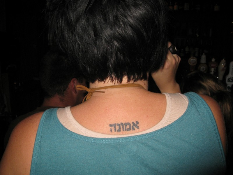 Small hebrew tattoo on back for women