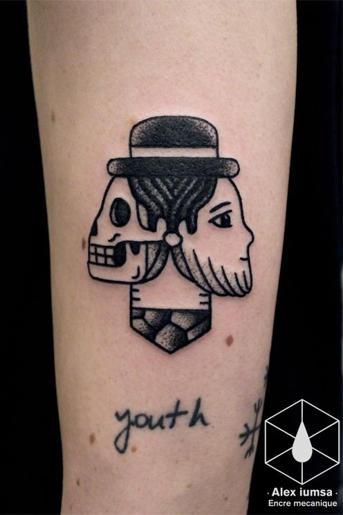 Small homemade style arm tattoo of interesting figure and lettering
