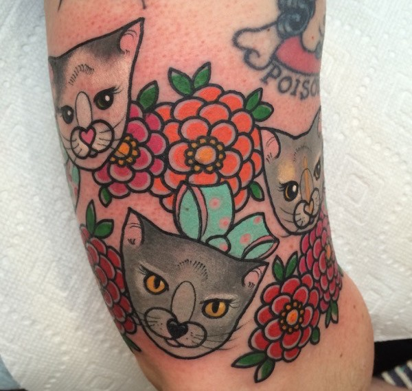 Small illustrative style colored arm tattoo of cute kittens with flowers