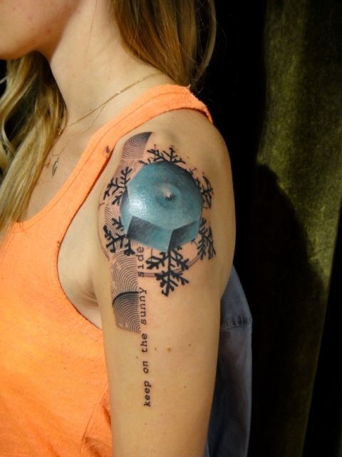 Small illustrative style colored shoulder tattoo of blue figure with snowflake and lettering