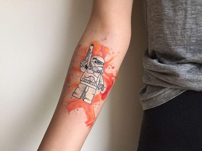 Small illustrative style forearm tattoo of Lego storm trooper