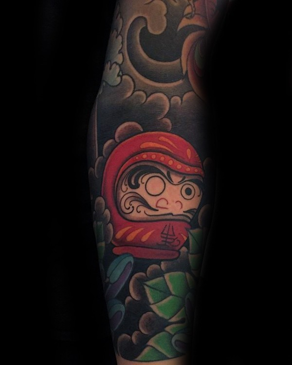 Small Lego style colored forearm tattoo of daruma doll