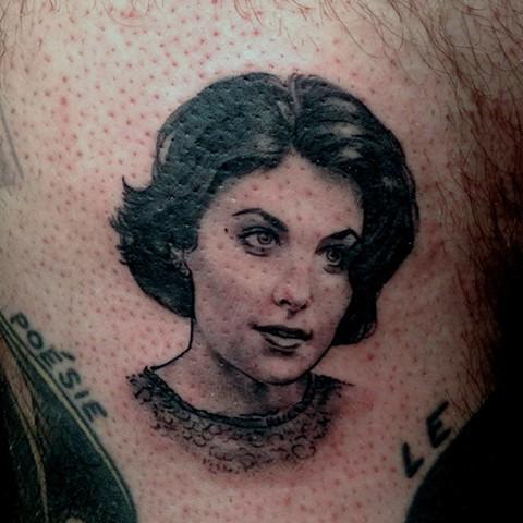 Small medium size tattoo on woman portrait