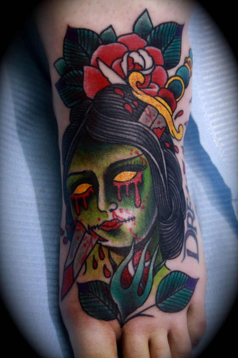 Small old school style colored bloody zombie head tattoo on foot with flowers and bloody