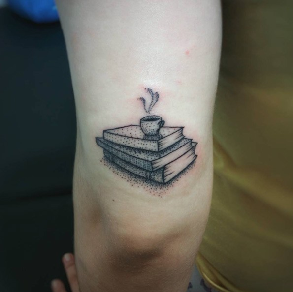 Small steaming mug on pale of books arm tattoo with tiny dots