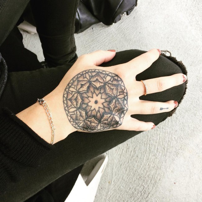 Small stippling style hand tattoo of flower