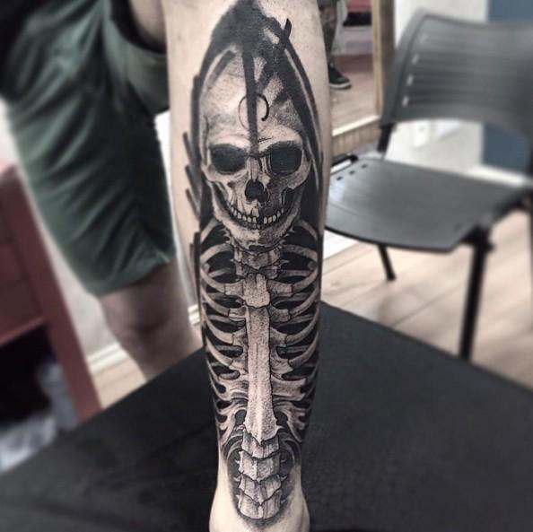 Smiling skull on skeleton black and white leg tattoo with dark shadow