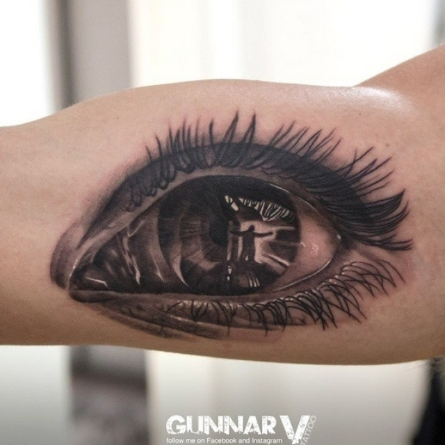 Spectacular black and white human eye tattoo on biceps