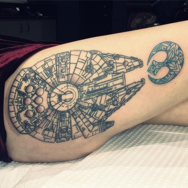 Spectacular black and white very detailed millennium falcon ship tattoo on thigh with Rebel Alliance emblem