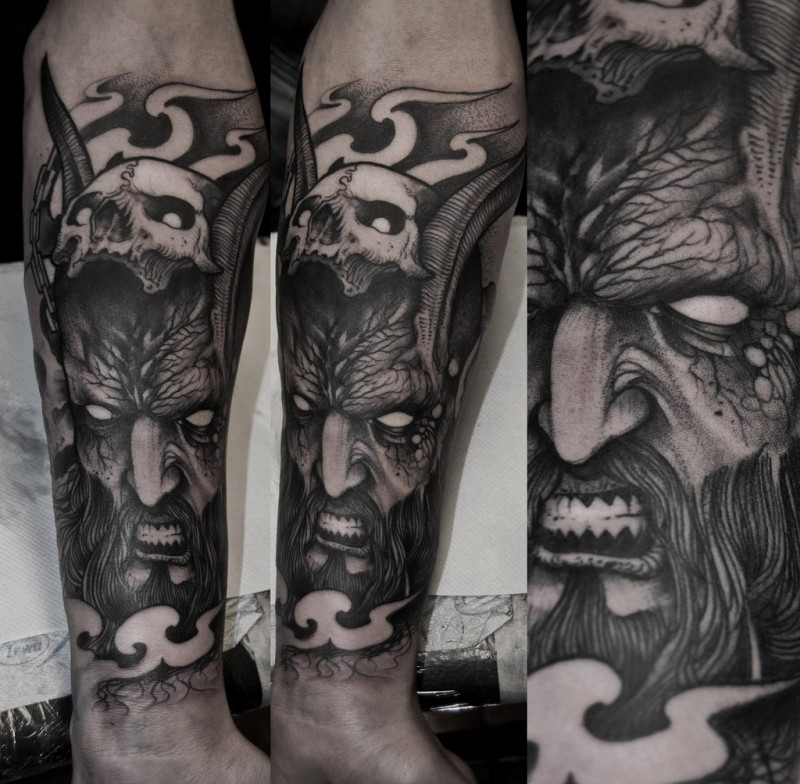 Spectacular black ink arm tattoo of demonic man with human skull