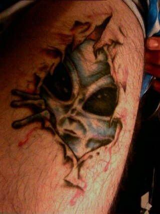 Spooky face alien skin rip tattoo