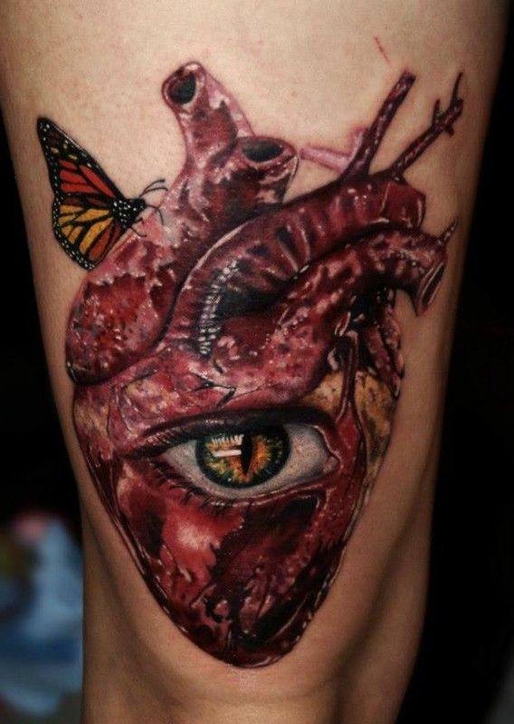 Tatuaggio sulla gamba il cuore con l&quotocchio e le farfalle