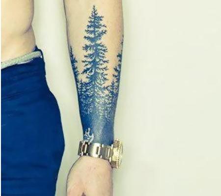 Tatuaggio curioso sul braccio gli alberi blu