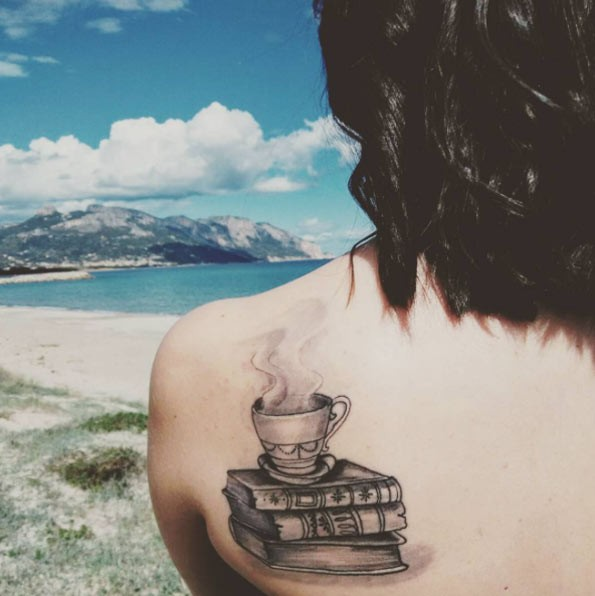 Steaming cup on pale of books detailed black and white upper back tattoo