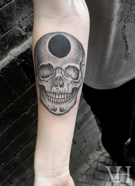 Stippling style black and white forearm tattoo of skull with black whole