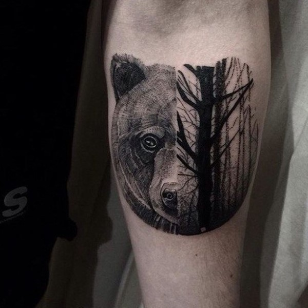 Stippling style black and white forearm tattoo of bear head with dark forest