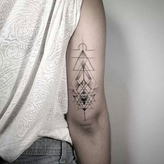 Stippling style black ink arm tattoo of geometrical figures