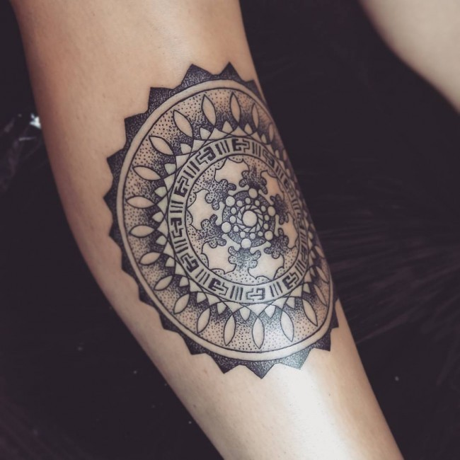 Stippling style black ink arm tattoo of circle shaped flower with lettering