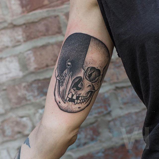 Stippling style black ink biceps tattoo of half human half birds skull