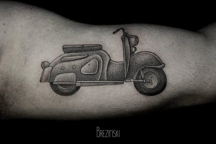 Stippling style black ink biceps tattoo of vintage scoter