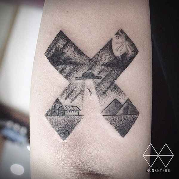 Stippling style black ink cross shaped arm tattoo stylized with alien ship stealing human