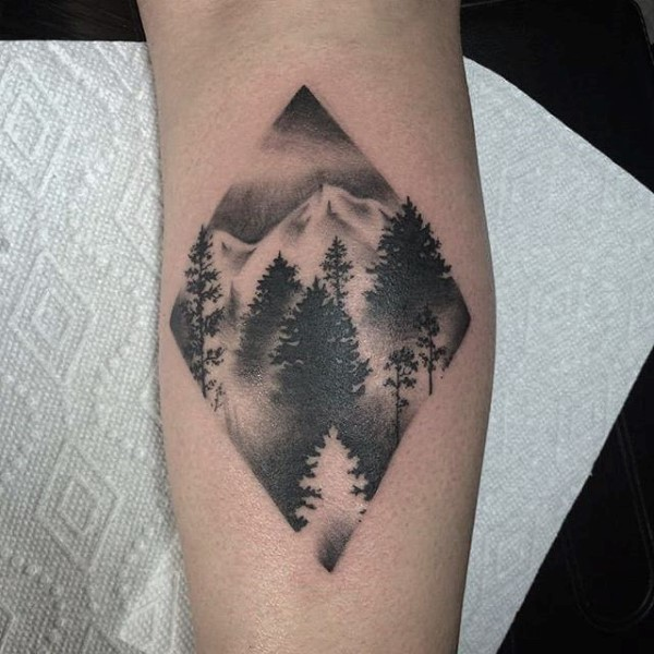 Stippling style black ink forearm tattoo of mountain forest