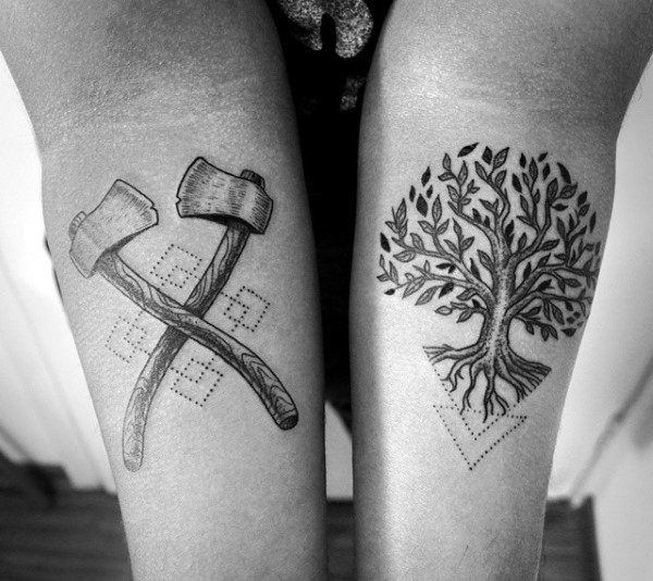 Stippling style black ink forearm tattoo of tree with crossed axes