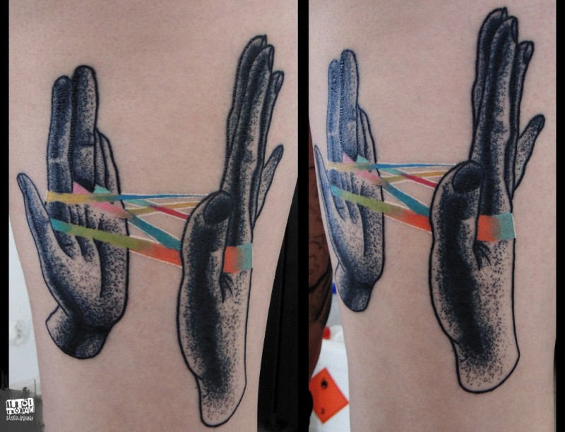 Stippling style black ink forearm tattoo of human hand with multicolored ribbon