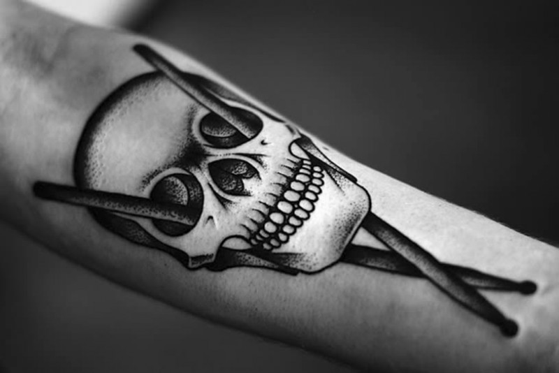 Stippling style black ink forearm tattoo of human skull with drum sticks