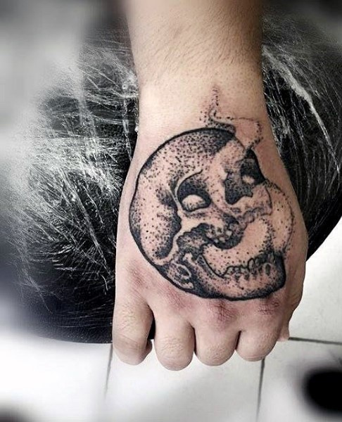Stippling style black ink hand tattoo of small skull and fog