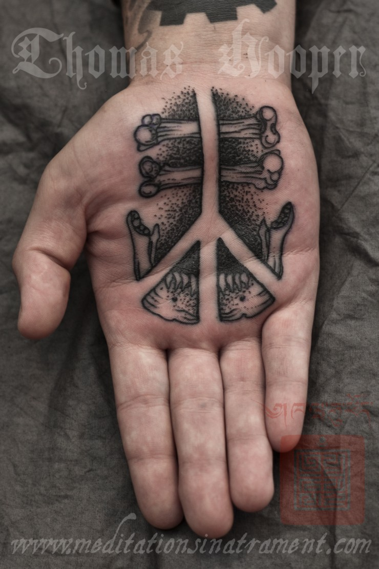 Stippling style black ink hand tattoo of pacific symbol with bones