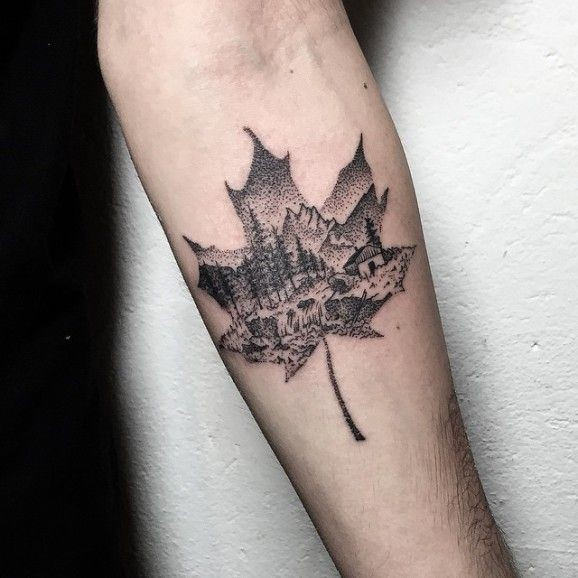 Stippling style black ink maple leaf shaped forearm tattoo stylized with mountain forest