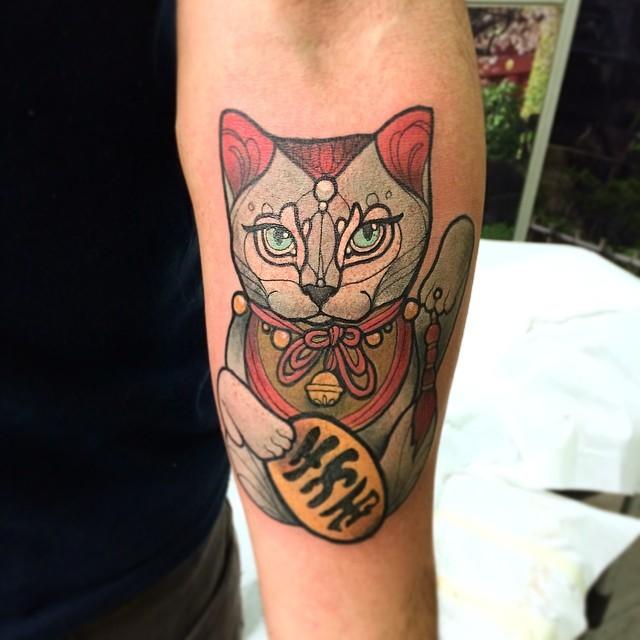 Stippling style colored forearm tattoo of maneki neko japanese lucky cat with symbol