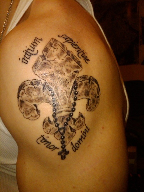 Stone fleur de lis with a rosary and inscriptions tattoo on shoulder