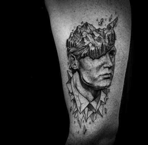 Stonework style black ink arm tattoo of man head with stone