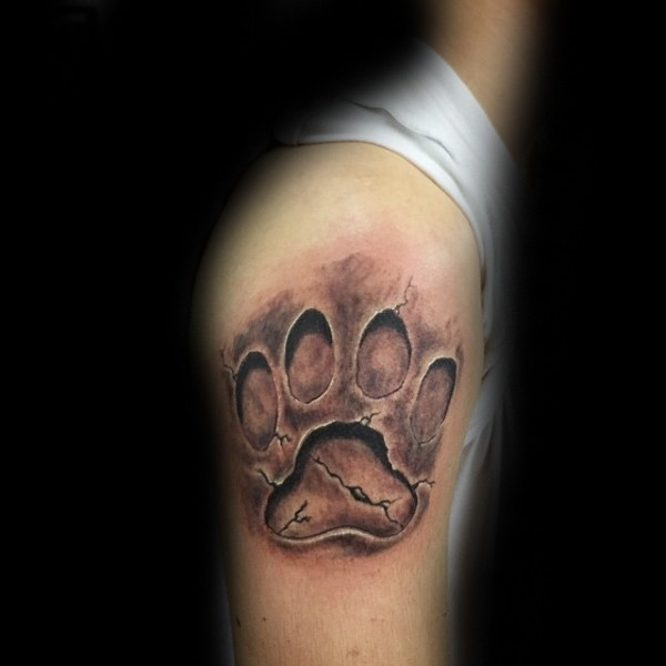 Stonework style black ink shoulder tattoo of big lion paw print
