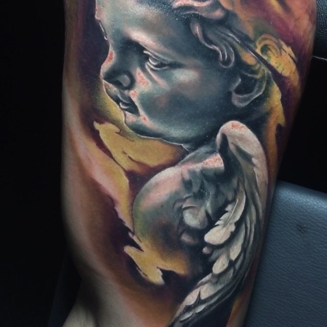 Stonework style colored biceps tattoo of small baby angel statue