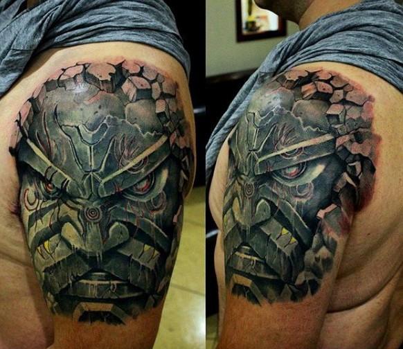 Stonework style colored shoulder tattoo of big mask