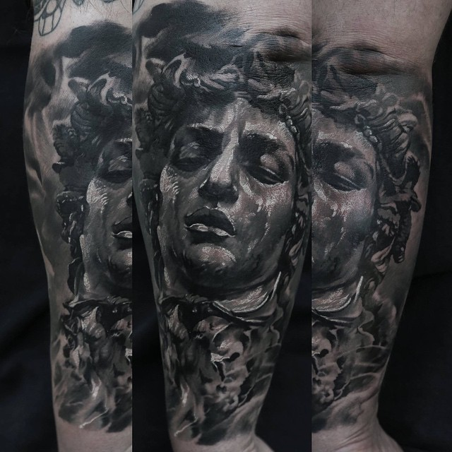 Stonework style detailed arm tattoo of big statue head
