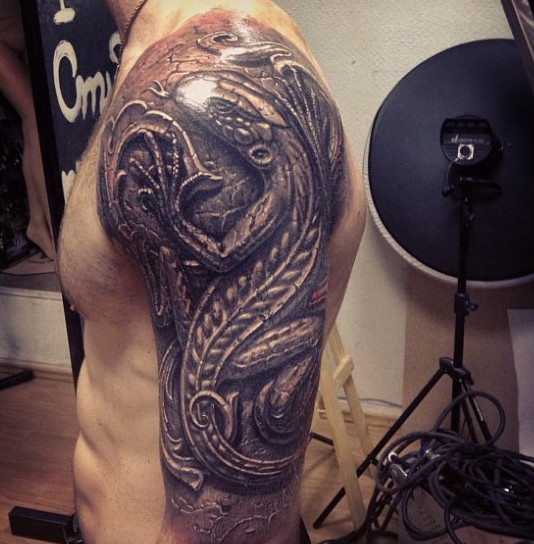 Stonework style detailed shoulder tattoo of big lizard wall statue