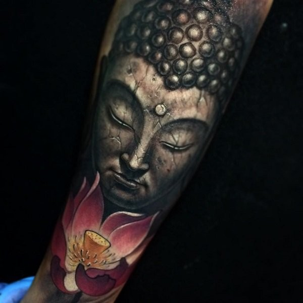 Stonework style forearm tattoo of Buddha statue and lotus flower