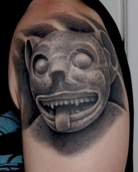 Stonework style shoulder tattoo of ancient demonic statue