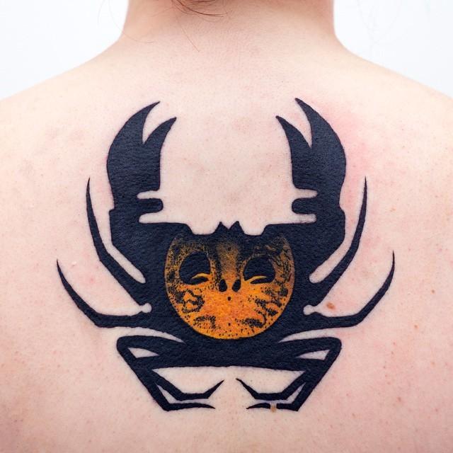 Strange designed black ink crab tattoo on upper back stylized with mystical symbol