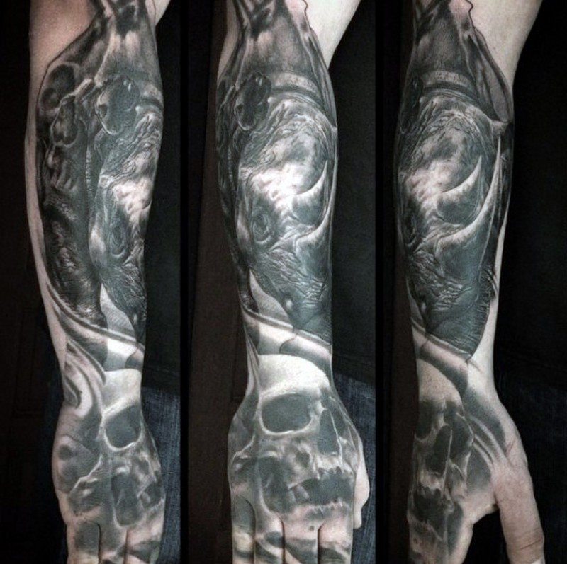 Strange looking black ink human skull tattoo on hand combined with rhino on forearm